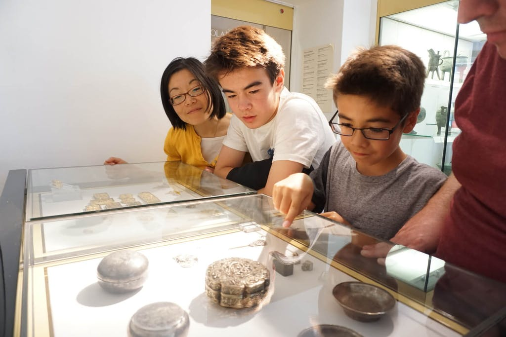 Family of four looking at object up close