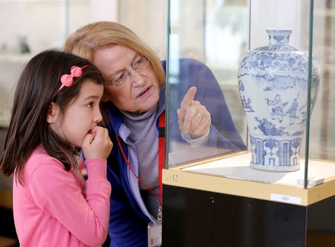 a gallery volunteer is explaining an object to a child at the Museum of East Asian Art