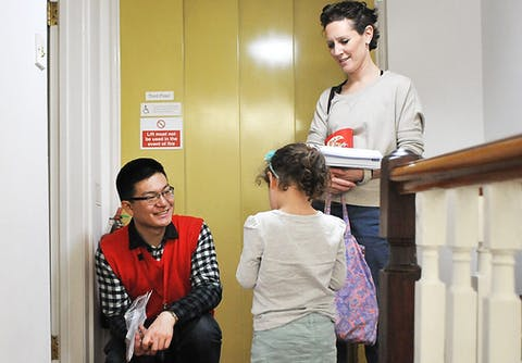 A volunteer is welcoming a family to attending an event
