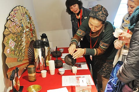 a volunteer in Mongolian costume helping in tea tasting during lunar new year celebration at the Museum of East Asian Art